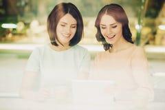 Δύο κορίτσια που μιλούν στον καφέ με τα φλιτζάνια του καφέ Στοκ εικόνα με δικαίωμα ελεύθερης χρήσης