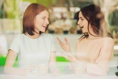 Δύο κορίτσια που μιλούν στον καφέ με τα φλιτζάνια του καφέ Στοκ Εικόνα