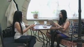 Δύο κορίτσια που μιλούν σε έναν καφέ και πίνουν τον καφέ απόθεμα βίντεο