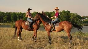 Δύο κορίτσια που οδηγούν στα καφετιά άλογα κοντά σε μια λίμνη φιλμ μικρού μήκους