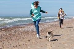 Δύο κορίτσια που οργανώνονται με το σκυλί Στοκ Φωτογραφίες