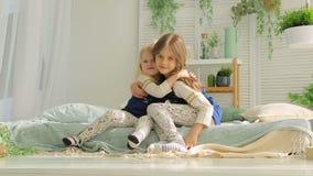 Δύο κορίτσια που παίζουν στο δωμάτιο στο κρεβάτι και το αγκάλιασμα απόθεμα βίντεο