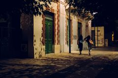Δύο κορίτσια που περπατούν κάτω από την οδό τη νύχτα στοκ φωτογραφίες