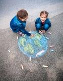 Δύο κορίτσια που σύρουν τη γη με τις κιμωλίες Στοκ φωτογραφίες με δικαίωμα ελεύθερης χρήσης