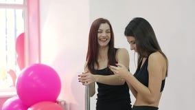 Δύο κορίτσια που χαμογελούν κρατώντας ένα κινητό τηλέφωνο στη γυμναστική Μικρή διακοπή κατά τη διάρκεια της κατάρτισης Πρόσωπα χα απόθεμα βίντεο