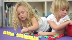 Δύο κορίτσια που χρησιμοποιούν τα πλαστικά πρότυπα παιχνίδια στην κατηγορία μαθηματικών απόθεμα βίντεο