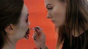 Δύο κορίτσια προετοιμάζονται για αποκριές Τρομακτική κυρία Visage με ένα ragged αιματηρό στόμα Ο όμορφος καλλιτέχνης makeup εφαρμ απόθεμα βίντεο