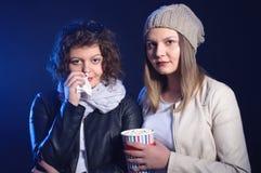 Δύο κορίτσια προσέχουν το ρομαντικό κινηματογράφο στον κινηματογράφο Στοκ Φωτογραφίες