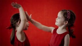 Δύο κορίτσια στέλνουν ένα φιλί σε ένα κόκκινο υπόβαθρο φιλμ μικρού μήκους