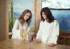 Δύο κορίτσια στα άσπρα παλτά μετά από μια σάουνα Στοκ εικόνες με δικαίωμα ελεύθερης χρήσης