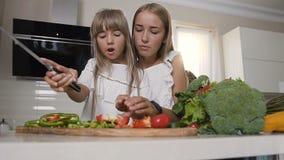Δύο κορίτσια στα άσπρα φορέματα είναι τέμνοντα λαχανικά στο σπίτι στην κουζίνα Δύο γοητευτικά κορίτσια που προετοιμάζουν τη σαλάτ φιλμ μικρού μήκους