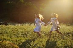 Δύο κορίτσια στα εθνικά ουκρανικά ενδύματα με τα στεφάνια της ροής Στοκ Εικόνες