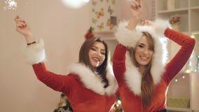 Δύο κορίτσια στα κοστούμια του νέου έτους που χορεύουν με τα σπινθηρίσματα εσωτερικά 4K φιλμ μικρού μήκους