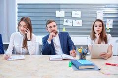 Δύο κορίτσια στην εργασία στο γραφείο, και το άτομο εξετάζουν την απόσταση στοκ φωτογραφίες