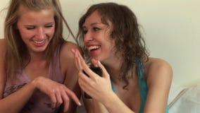 Δύο κορίτσια στην κρεβατοκάμαρα με ένα Iphone απόθεμα βίντεο