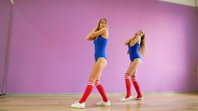 Δύο κορίτσια στον μπλε χορό κοστουμιών λουσίματος στα πλαίσια ενός πορφυρού τοίχου Τα κορίτσια στο ύφος disco χορεύουν προκλητικό απόθεμα βίντεο