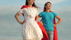 Δύο κορίτσια στους κόκκινους επενδύτες της στάσης superheroes ενάντια σε έναν μπλε ουρανό, ο αέρας διογκώνουν έναν επενδύτη Παιχν απόθεμα βίντεο