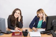 Δύο κορίτσια στο γραφείο που μιλά στα κινητά τηλέφωνα Στοκ Εικόνες