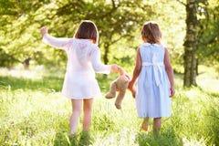 Δύο κορίτσια στο πεδίο που φέρνει Teddy αντέχουν Στοκ φωτογραφία με δικαίωμα ελεύθερης χρήσης