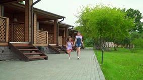 Δύο κορίτσια της φίλης που οργανώνεται στο πεζοδρόμιο στο πάρκο Όμορφα κορίτσια που οργανώνονται στη κάμερα απόθεμα βίντεο