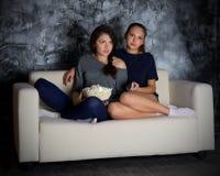 Δύο κορίτσια φαίνονται TV Στοκ Φωτογραφίες