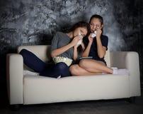 Δύο κορίτσια φαίνονται TV Στοκ Εικόνες