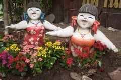 Δύο κορίτσια χαμογελούν το γλυπτό με τα ζωηρόχρωμα λουλούδια Στοκ εικόνα με δικαίωμα ελεύθερης χρήσης