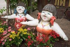 Δύο κορίτσια χαμογελούν το γλυπτό με τα ζωηρόχρωμα λουλούδια Στοκ φωτογραφία με δικαίωμα ελεύθερης χρήσης