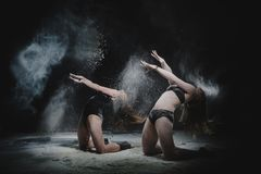 Δύο κορίτσια χορεύουν με το αλεύρι στο στούντιο στο μαύρο υπόβαθρο, τα φω'τα πίσω από τους και ενισχυμένα τα άνθρωποι κορίτσια στοκ εικόνα