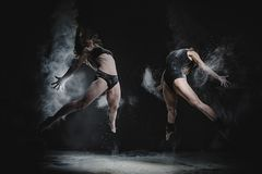 Δύο κορίτσια χορεύουν με το αλεύρι στο στούντιο στο μαύρο υπόβαθρο, τα φω'τα πίσω από τους και ενισχυμένα τα άνθρωποι κορίτσια στοκ φωτογραφία με δικαίωμα ελεύθερης χρήσης