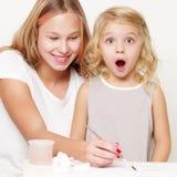 Δύο κορίτσια χρωματίζουν σε ένα κομμάτι χαρτί στοκ εικόνες με δικαίωμα ελεύθερης χρήσης