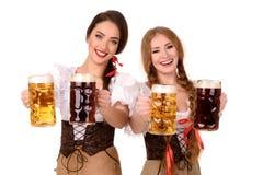 Δύο κορίτσια όμορφων ξανθά και brunette της πιό oktoberfest μπύρας stein Στοκ Φωτογραφίες