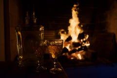 Δύο κούπες γυαλιού του ζεστού ποτού ή του οινοπνευματώδους ποτού μπροστά από τη θερμή εστία στοκ φωτογραφία