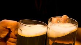 Δύο κούπες της ελαφριάς μπύρας αφρού είναι στα χέρια δύο ανθρώπων Στοκ Φωτογραφίες