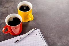 Δύο κούπες του καφέ κοντά στο σημειωματάριο στοκ φωτογραφίες