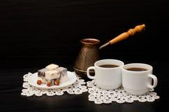 Δύο κούπες του καφέ, τουρκικό lokum με το φουντούκι, Cezve σε ένα μαύρο υπόβαθρο Στοκ εικόνες με δικαίωμα ελεύθερης χρήσης