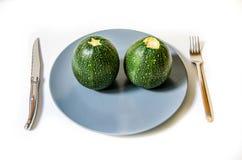 Δύο κολοκύθια στη μέση ενός πιάτου Στοκ Εικόνες