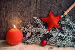 Δύο κόκκινα κεριά με το ντεκόρ Χριστουγέννων στο ξύλινο υπόβαθρο Στοκ Φωτογραφία