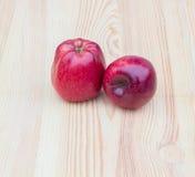 Δύο κόκκινα μήλα σε ένα ξύλινο υπόβαθρο Στοκ φωτογραφία με δικαίωμα ελεύθερης χρήσης