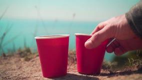 Δύο κόκκινα μίας χρήσης φλυτζάνια του τσαγιού ή του καφέ στα πλαίσια της θάλασσας και του ορίζοντα φιλμ μικρού μήκους