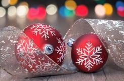 Δύο κόκκινα μπιχλιμπίδια Χριστουγέννων και ζωηρόχρωμα φω'τα Στοκ φωτογραφία με δικαίωμα ελεύθερης χρήσης
