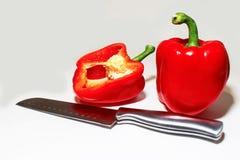 Δύο κόκκινα πιπέρια ένας κομμένοι ανοικτός και μαχαίρι μπροστά από και τα δύο στοκ εικόνα με δικαίωμα ελεύθερης χρήσης