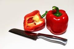 Δύο κόκκινα πιπέρια, ένας κομμένος ανοικτός και ένα μαχαίρι στο μέτωπο στοκ εικόνα με δικαίωμα ελεύθερης χρήσης
