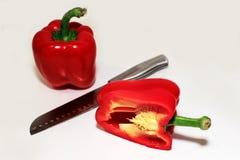 Δύο κόκκινα πιπέρια, ένας κομμένος ανοικτός με το μαχαίρι μεταξύ στοκ φωτογραφίες