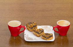 Δύο κόκκινα φλιτζάνια του καφέ και κέικ Στοκ εικόνα με δικαίωμα ελεύθερης χρήσης