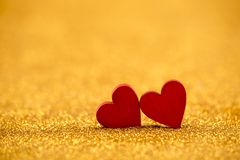Δύο κόκκινες καρδιές σε χρυσό ακτινοβολούν ερωτευμένη έννοια υποβάθρου στοκ φωτογραφία