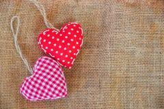 Δύο κόκκινες καρδιές υφάσματος στον αγροτικό καμβά Στοκ Εικόνα
