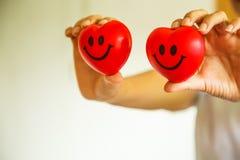 Δύο κόκκινες καρδιές χαμόγελου που κατέχουν τα θηλυκά χέρια νοσοκόμων ` s, που αντιπροσωπεύουν δίνοντας την προσπάθεια υψηλή - μυ Στοκ Εικόνα
