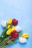 Δύο κόκκινες καρδιές και κίτρινα και άσπρα λουλούδια τουλιπών στο μπλε tex Στοκ Εικόνες