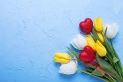 Δύο κόκκινες καρδιές και κίτρινα και άσπρα λουλούδια τουλιπών στο μπλε tex Στοκ εικόνα με δικαίωμα ελεύθερης χρήσης